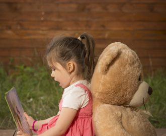 Little girl with toy bear sitting outside in backyard playground, reading to her little plush friend